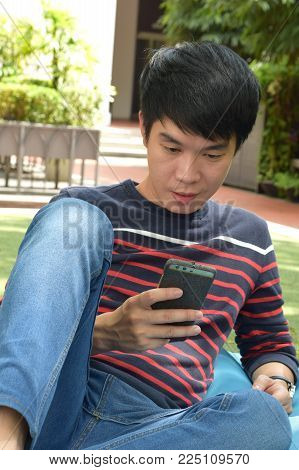 A young asian chinese looking at his mobile phone outdoor