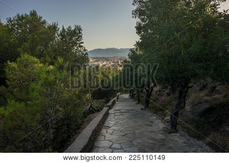 Stone Pathway Leading Down The Hill Overlooking Malaga, Spain, Europe With Trees On Eiher