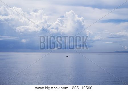 Sea and sky double landscape. Seashore view with fishing boat. Cloudy sky and calm sea. Summer weather on tropical island. Exotic seaside travel destination place. Relaxing seaside banner. Calm coast