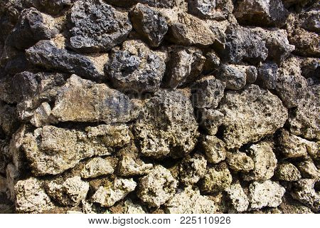 Rough stone solid wall closeup photo. Stone wall texture. Rustic stone wall of ancient building. Grey weathered rock closeup. Durable old masonry stonewall pattern. Distressed texture of rock paving