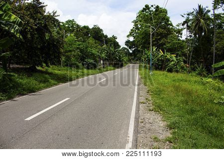 Empty asphalt road in tropical countryside with green bush on roadside. Highway on tropical island. Empty road by jungle. Tropical forest. Road landscape. Summer holiday travel banner. Island hopping