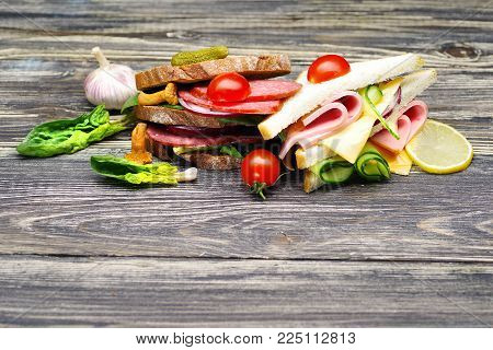 Fresh appetizing sandwiches with salami, vegetables, ham and cheese on a wooden table.