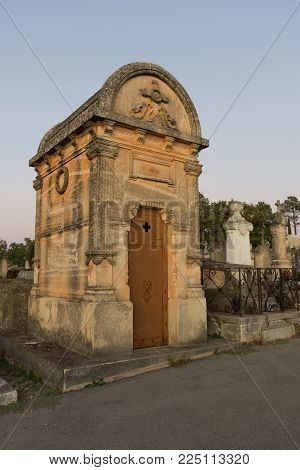 A Mausoleum Made Of Local Gold Colored Stone In A Cemetery In Roussillon France.  An Ornate Cross Is