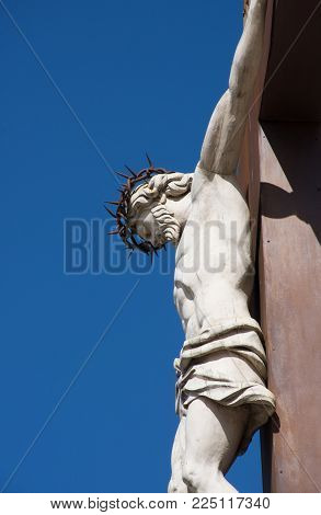 A Statue Of The Crucified Jesus Hanging From A Cross And Wearing A Crown Of Thorns. The Statue Is At