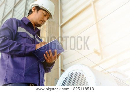 Asian engineer or technician in safety uniform and white helmet checking motor gear machinery equipment and writing data on notebook with sun light effect for industrial concept
