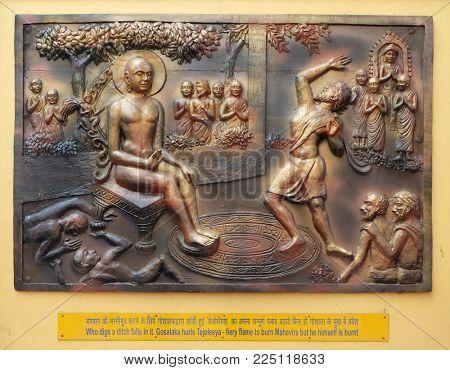 KOLKATA,INDIA - FEBRUARY 09, 2016: Who digs a ditch falls in it. Gosalaka hurls Tejolesya - fiery flame to burn Mahavira but he himself is burnt, relief on the wall of Jain Temple in Kolkata