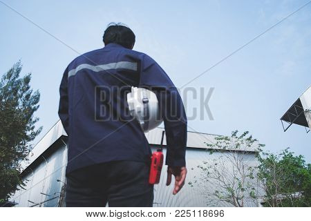 Blur foreground image of asian engineer in safety uniform holding white security helmet and walkie-talkie against industry plant and blue sky background for industrial concept