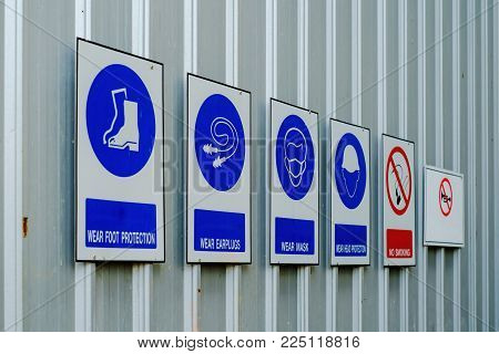 Safety clothing or personal protective equipment and prohibition signs in hazardous areas of work site for industrial concept