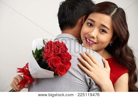 Adorable Asian woman looking at camera with deep gray eyes while embracing her soulmate, isolated on white background
