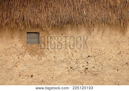 earth house with window natural building and straw roof background