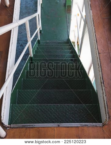 Deck of moored passenger transport ship on the embankment with white handrail to the cabins and green stairs