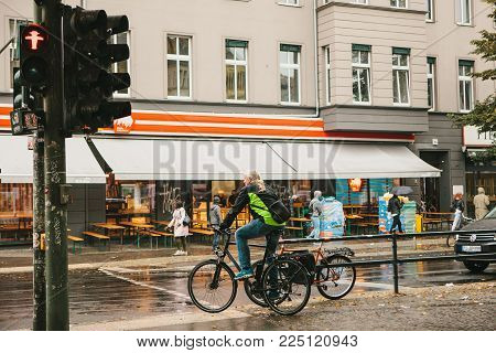 Berlin, October 1, 2017: An Elderly Man On A Bicycle Stands On A Red Traffic Light And Waits For Him