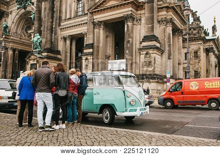 Berlin, October 1, 2017: Group Of Young Unknown Tourists Book Tourist Trip On Blue Retro Mini Bus Ne