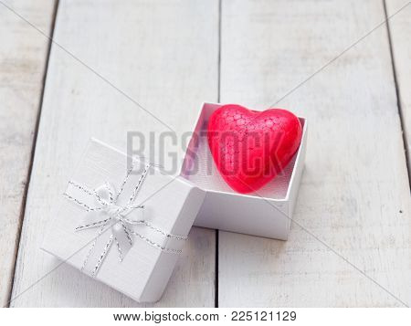Red heart inside white gift box over white wooden background with concept of love and romance