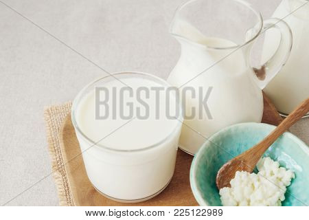 Organic Probiotic Milk Kefir Grains, Tibetan Mushrooms On Wooden Spoon Over Kefir Milk In A Glass