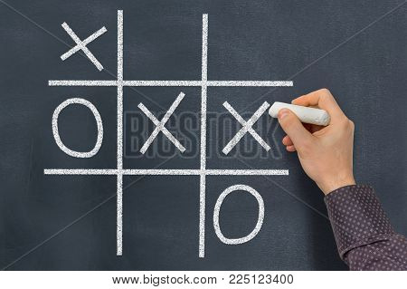 Tic-tac-toe game on blackboard in classroom - education concept