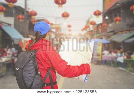 Beautiful woman traveler holding location map in hands.Traditional being sold at chinese chinatown outdoor market.