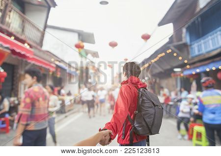 Man traveler holding hand of wife following him withTraditional being sold at chinese chinatown outdoor market.