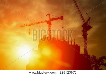 Silhouette of tower cranes and building silhouettes over sun at sunrise.