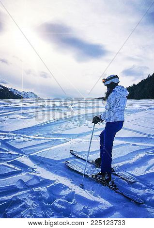 Woman skier skiing downhill during sunny day in high mountains.
