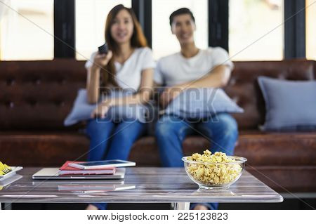 Happy asian young couple loving on the couch watching a movie together,Woman holding remote and her husband sittind next to her.Close up popcorn.