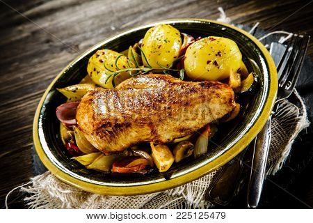 Roast chicken breast with potatoes on wooden background