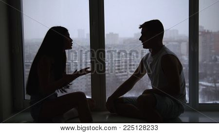 Young family couple sitting on the windowsill, emotionally talking, arguing and gesticulating, relationship between people, silhouette shot