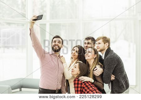 friendly business team makes a selfie standing near the window in the spacious office