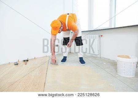 worker gluing wood parquet floor.