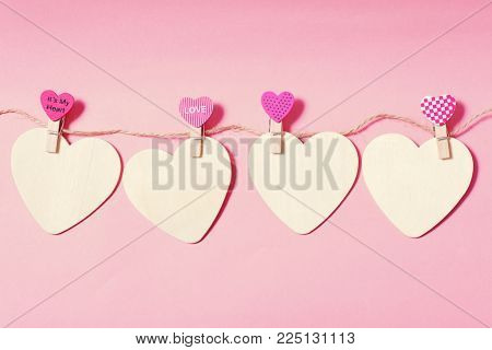 White hearts with clothes pegs on pink background, Valentine concept