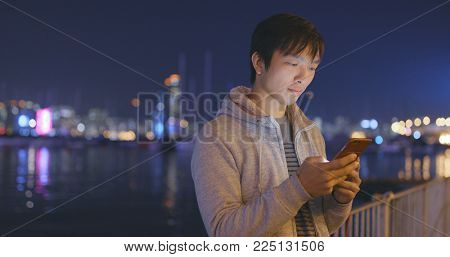 Young Man using smart phone in city at night