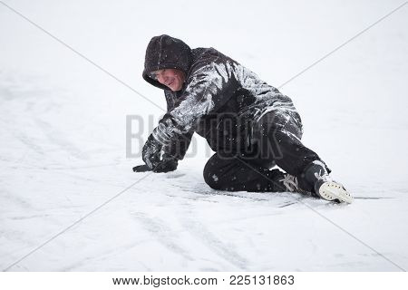 The man fell on skates in the snow.An elderly man learns to ride a hockey skate