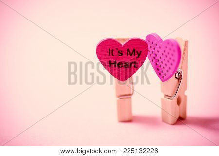 Decoration clothes pegs (heart shape) on pink background, Valentine concept