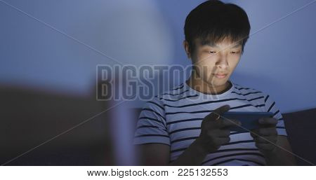 Man playing mobile game on cellphone at night