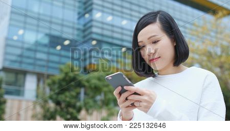 Woman sending audio message over business building background