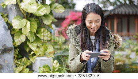 Woman playing game on cellphone at china, chinese garden