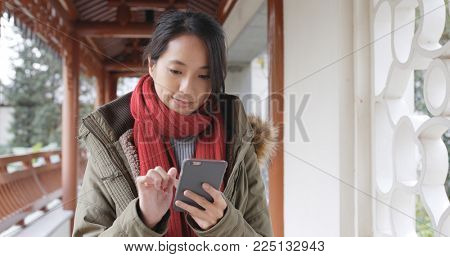 Woman use of mobile phone at china, woman wearing winter jacket at outdoor