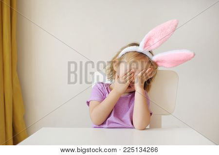 the girl with ears of a rabbit takes offense, hides the face in hands.