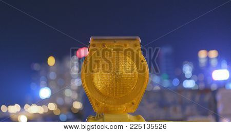Caution yellow light in the city at night