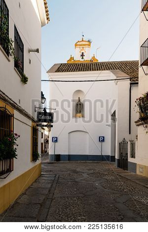 Cordoba, Spain - April 10, 2017: Old typical street in the Alcazar Viejo quarter of Cordoba near San Basilio Church. This quarter is famous for his decorated with flowers courtyards or patios
