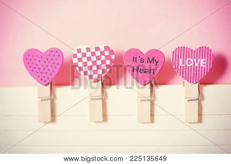 Decoration clothes pegs (heart shape) with paper on pink background, Valentine concept