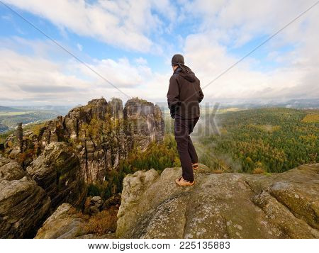 Sportsman in black with hands in pockets stand on the peak in rock empires park and watching over the misty and foggy morning valley to Sun. Silhouette of man. Hiker deep think with hands in pocket.