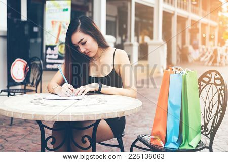 Asian woman hand checking shopping list on desk at outside outlet mall.