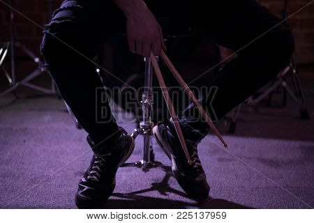 Close up of Drummer hands holding drumstick  and sitting next to drum kit.Rock musician taking a rest after the rehearsing