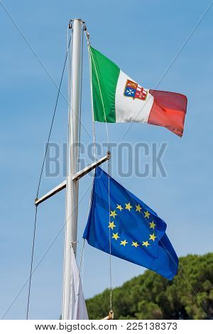 European and Italian flag with emblem of the four Maritime Republics, Venice, Genoa, Pisa and Amalfi hanging on a ship's mast on blue sky