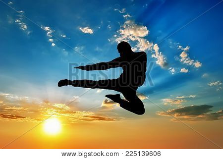 silhouette of а man flying kick in sunset sky background. Martial arts composition.