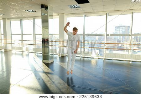 Boyfriend shoot video from training for girlfriend, hip-hop dancer energetically moving for camera. Handsome tattooed guy wearing white sport clothes in hall with big windows. Concept of choreographic school, well-equipped gym or man sportswear