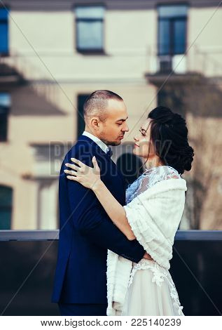 Wedding photo shooting. Bride and bridegroom walking in the city. Man embracing girl's.