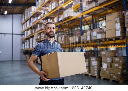 Young male warehouse worker or a supervisor holding a large box.