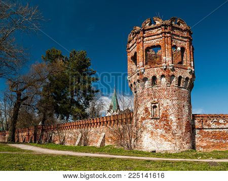 Part of the architectural complex Fedorovsky town with a collapsed brick wall and a watchtower in Tsarskoe Selo in the Alexander Park in the spring of May in St. Petersburg, Russia